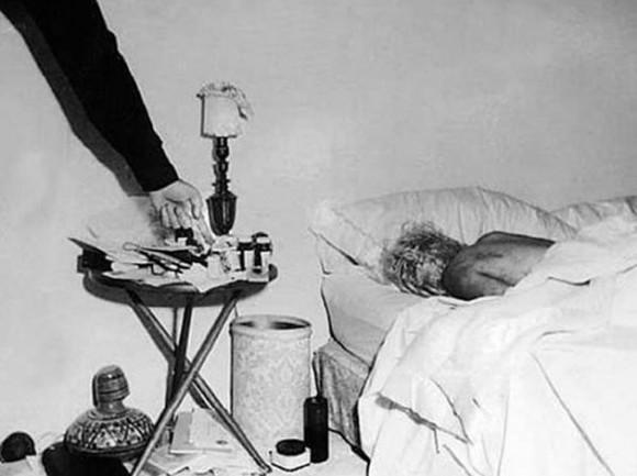 Fotografía inédita del cadáver de Marilyn Monroe en el dormitorio de su casa. Un policía, probablemente el sargento Jack Clemmons, señala las pastillas que provocaron la muerte de la actriz. LOS ANGELES PUBLIC LIBRARY, NICK BOUGAS, JAMES MASON. Cedida por la editorial GLOBAL RHYTHM PRESS