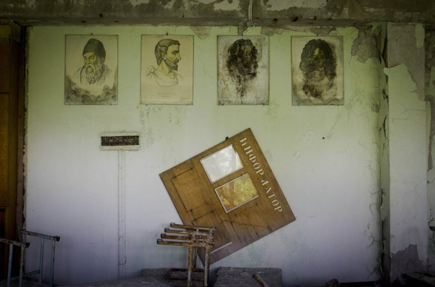 Portraits of ancient physicists and mathematicians hang on a wall in a school in the deserted town of Pripyat, Ukraine, some 3 kilometers (1.86 miles) from the Chernobyl nuclear plant. Chernobyl and Fukushima are some 5,000 miles apart but have much in common. The towns nearest to each of these stricken nuclear power stations, in Ukraine and Japan, whose disasters struck 25 years apart, already reveal eerie similarities. (AP Photo/Sergey Ponomarev)