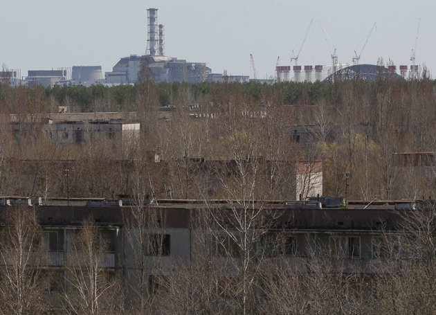 A containment shelter for the damaged fourth reactor (L) and the New Safe Confinement (NSC) structure (R) at the Chernobyl Nuclear Power Plant are seen from Ukraine's abandoned town of Pripyat April 23, 2013. Ukraine will mark the 27th anniversary of the Chernobyl disaster, the world's worst civil nuclear accident, on April 26. The NSC, to be placed over the existing sarcophagus, will have a span of 247 meters (270 yards) and weigh 29,000 tonnes when fully assembled, according to the European Bank of Reconstruction and Development. REUTERS/Gleb Garanich