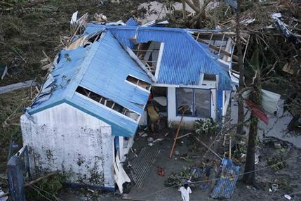 Pobladores revisan los escombros de su vivienda dañada por el paso de un poderoso tifón en la ciudad de Tacloban, de la provincia de Leyte, Filipinas, el sábado 9 de noviembre de 2013. (Foto AP/Bullit Márquez)