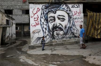 Palestinos pasan junto a un mural con la imagen del líder palestino Yasser Arafat en el campamento de refugiados Shati en la Ciudad d eGaza el 7 de noviembre del 2013. Científicos suizos hallaron evidencias de que Arafat pudo haber sido envenenado con una sustancia radiactiva, informó una emisora televisiva ese mismo día (AP Foto/Adel Hana)
