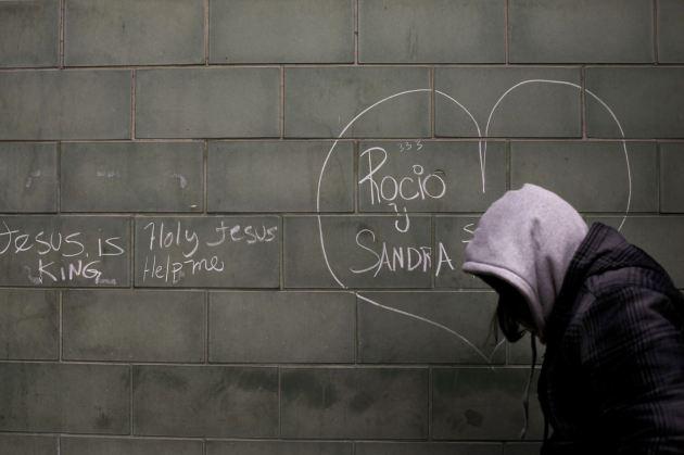 Una mujer camina por la calle junto a la pared de un refugio para personas sin casa en Skid Row, Los Ángeles. (AP/Jae C. Hong).