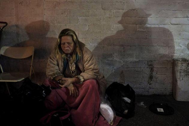 Una mujer sin hogar come una pieza de fruta en la calle, mientras que el reflejo de la pared muestra la figura de otros dos vagabundos. (AP/Jae C. Hong).