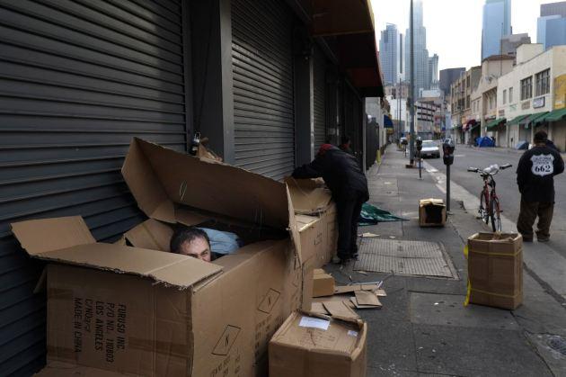 Antonio Garcia, que se presenta a sí mismo como un matemático, se asoma en su refugio improvisado de cajas de cartón en Skid Row, Los Ángeles. (AP/Jae. C. Hong)