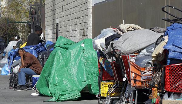 Una persona sin hogar, sentada en la calle entre sus posesiones en Los Ángeles (AP)