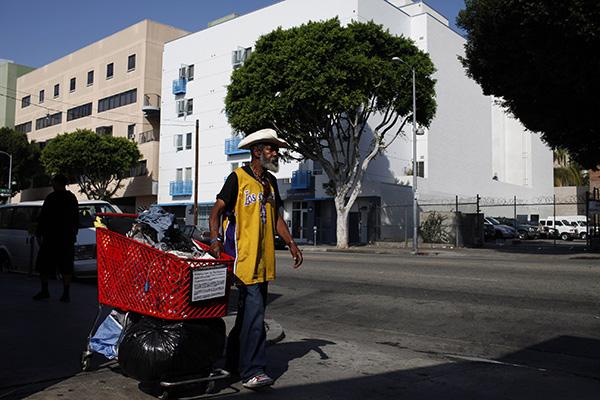 Un hombre sin hogar transporta un carrito con sus pertenencias por Los Ángeles (AP)
