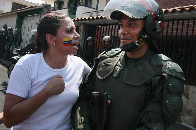 Una manifestante le habla a un policía durante una marcha contra el gobierno de Nicolás Maduro en San Cristobal, Táchira