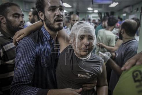 Un padre ayuda a su hijo, herido en el bombardeo israelí a la escuela de la localidad de Beit Hanún, en el hospital de Kamal Adwan en Beit Lahiya en Gaza. EFE/Archivo