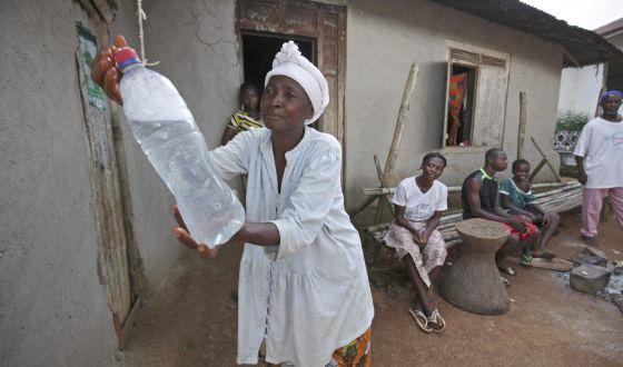 Una mujer se lava las manos con agua clorada, una medida de prevención ante el ébola, en Sierra Leona / AHMED JALLANZO (EFE)