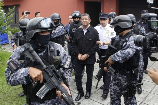 Agentes de la Policía Nacional Civil custodian al expresidente de El Salvador Francisco Flores (c) durante su traslado a una celda policial hoy, viernes 19 de septiembre de 2014, en San Salvador. EFE