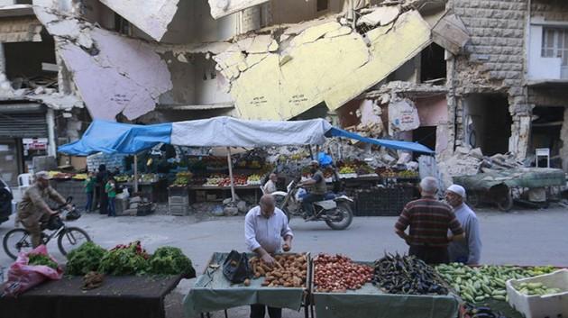 Residentes de la ciudad siria de Alepo compran verduras y frutas frente a un edificio dañado en el barrio de Bustan al-Qasr / Hosam Katan / Reuters